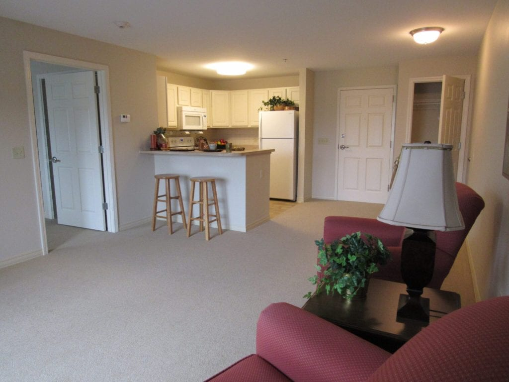 A one-bedroom apartment at the Terrace Retirement Community with an open kitchen, dining area and living room layout.
