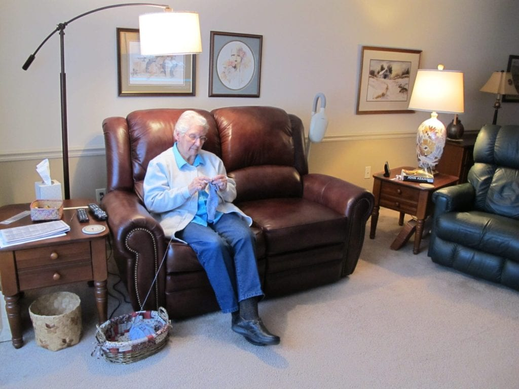 A Terrace Retirement Community resident knits on the couch in her private senior apartment.