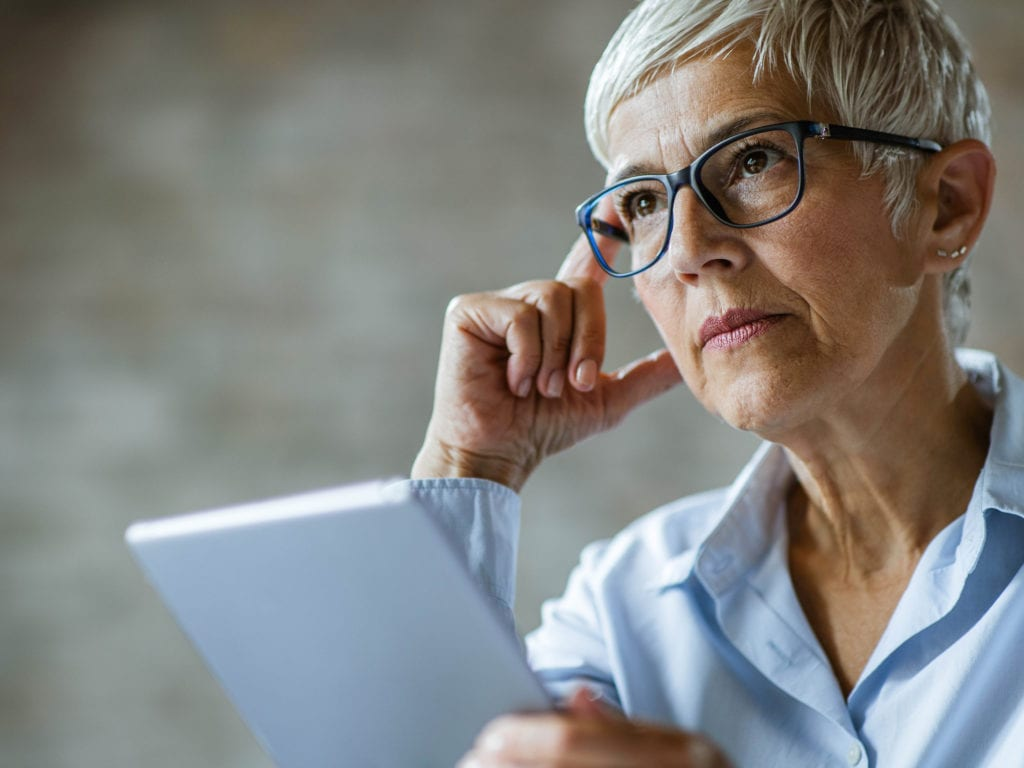 Concerned older woman with tablet computer