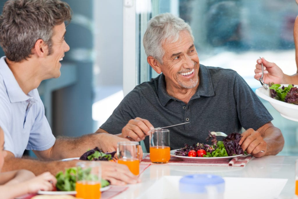 Mature man eating a salad for lunch with friends