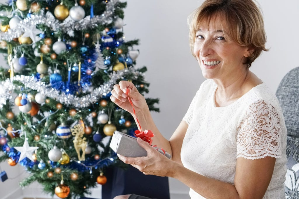 Mature woman opening a present in front of the Christmas tree