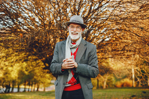 Handsome grandfather in a autumn park. Old man in a gray jacket and hat.